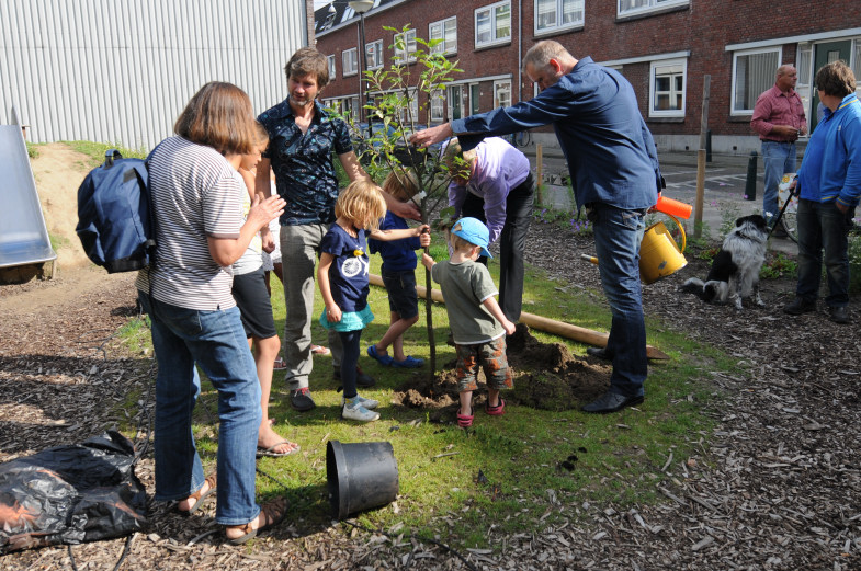 nils berndsen plant de boom. bewoners en kinderen houden de boom vast.