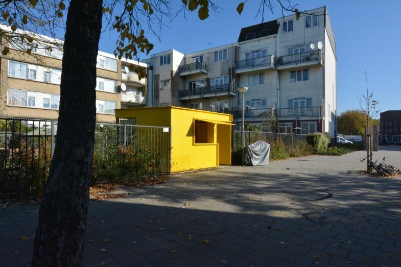 buurttuin met gele berging in straatbeeld